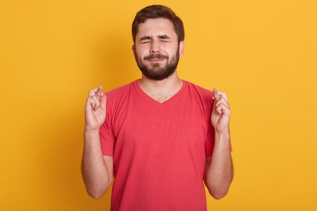 Feche o retrato de jovem bonito vestindo camiseta vermelha, mantendo os olhos fechados e os dedos cruzados
