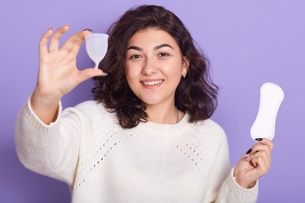 Feche o retrato de jovem escolhendo copo menstrual em vez de absorvente higiênico