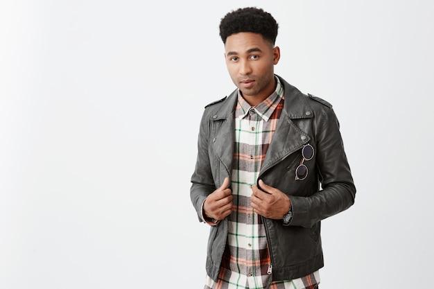 Feche o retrato de jovem estudante masculino americano de pele escura bonito com penteado afro na jaqueta de couro, segurando a roupa com as mãos com expressão confiante e relaxada.