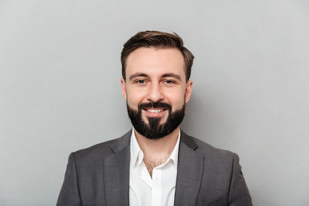 Feche o retrato de jovem homem barbudo na camisa branca e jaqueta posando na câmera com um amplo sorriso, isolado sobre cinza