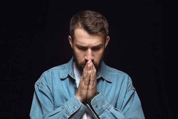 Feche o retrato de jovem isolado na parede preta. emoções reais do modelo masculino. rezando e chorando, parece triste e esperançoso. expressão facial, conceito de emoções humanas.