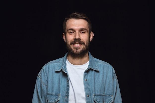 Feche o retrato de jovem isolado na parede preta. emoções reais do modelo masculino. sorrindo, me sentindo feliz. expressão facial, conceito de emoções humanas puras e claras.