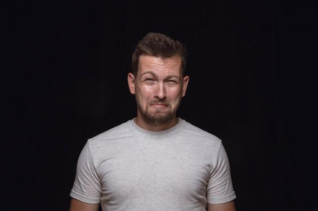 Feche o retrato de jovem isolado no espaço negro. photoshot de emoções reais do modelo masculino. chorando, triste, triste e sem esperança