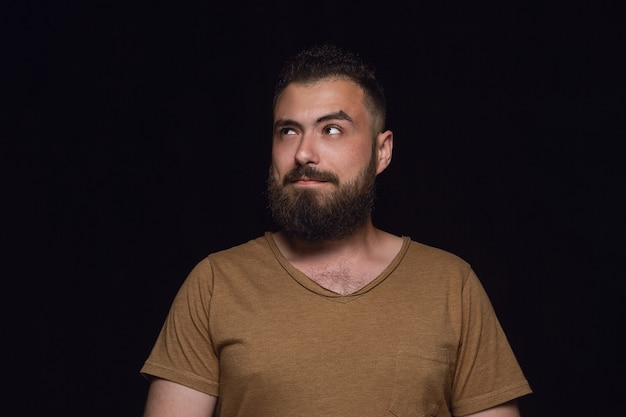 Feche o retrato de jovem isolado no fundo preto do estúdio. photoshot de emoções reais do modelo masculino. sonhando e sorrindo, esperançoso e feliz. expressão facial, conceito de emoções humanas.