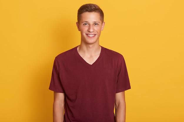 Feche o retrato de jovem satisfeito vestido marrom casual camiseta, olhando sorrindo para a câmera, expressa felicidade, modelo posando isolado em amarelo. conceito de pessoas, juventude e estilo de vida.