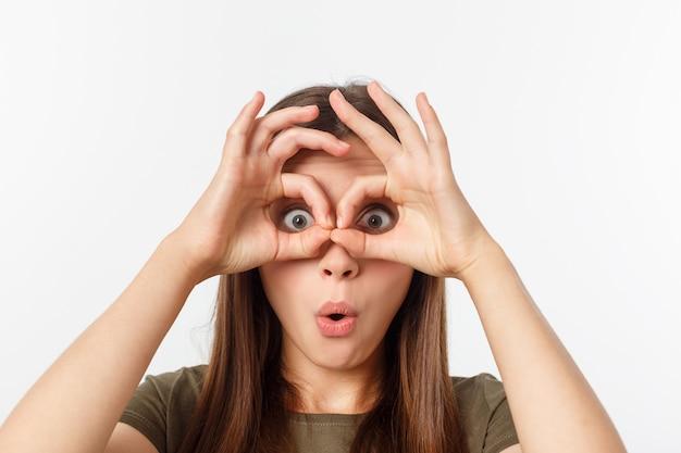 Feche o retrato de menina alegre, fofa, elegante, atraente, na moda, fazendo binóculos com os dedos, isolados no fundo cinza, de bom humor