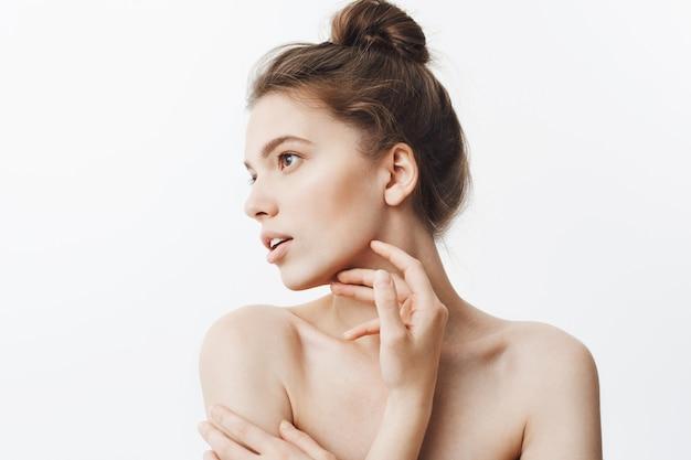 Feche o retrato de menina jovem estudante morena feminina com penteado de coque e ombros cozidos, olhando de lado com a expressão do rosto calmo, tocando o queixo com os dedos.