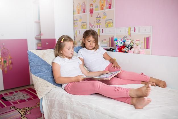 Feche o retrato de meninas adoráveis caucasianos lendo livro juntos no quarto acolhedor