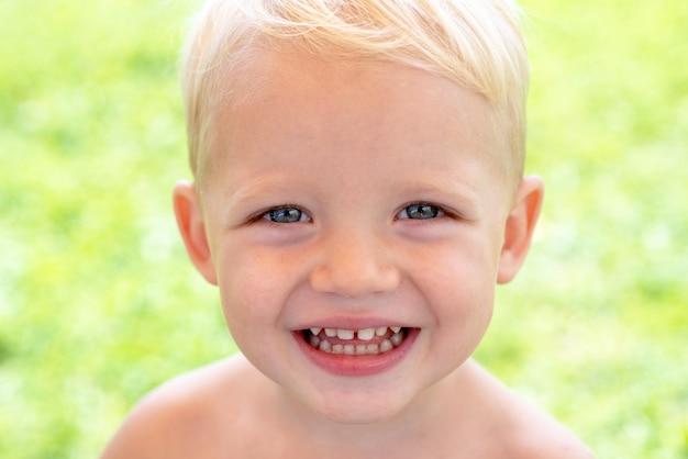 Feche o retrato de menino criança sorridente feliz no fundo verde da natureza