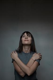 Feche o retrato de mulher, abraçando-se