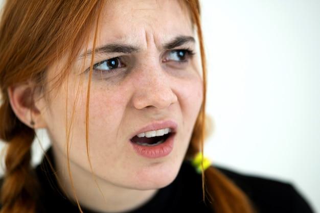 Feche o retrato de mulher adolescente ruiva com raiva.
