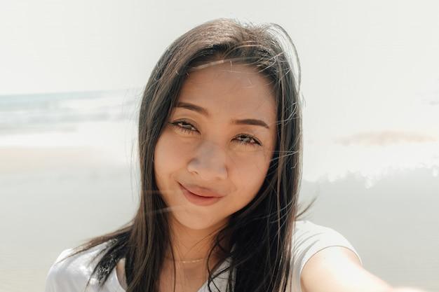 Feche o retrato de mulher ao ar livre na praia ensolarada no verão.