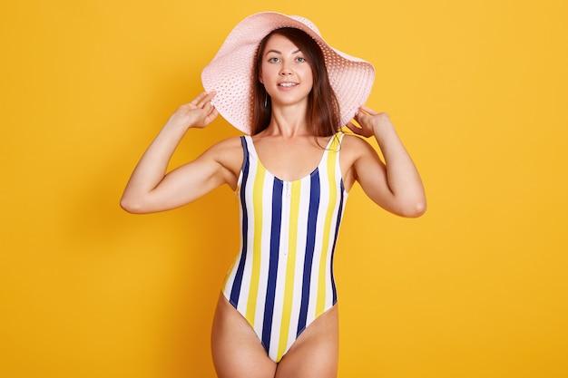 Feche o retrato de mulher bonita magro em traje de banho elegante e chapéu na moda, mantém as mãos em seu boné