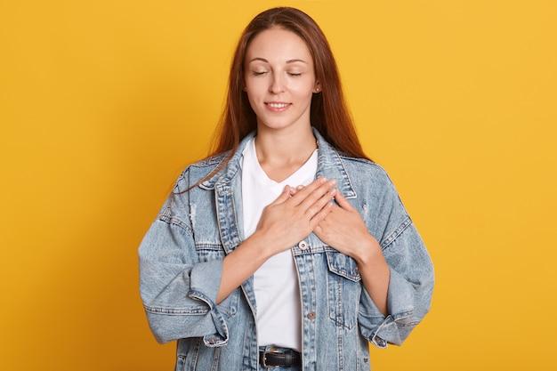 Feche o retrato de mulher bonita veste jaqueta jeans elegante e camiseta branca, em cima de amarelo isolado, em pé com as mãos no peito com os olhos fechados e gesto agradecido no rosto.