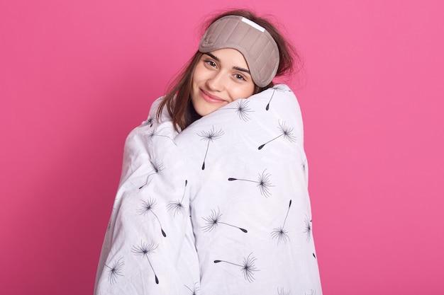 Feche o retrato de mulher com máscara de dormir na cabeça e vestindo cobertor olhando sorrindo para a câmera
