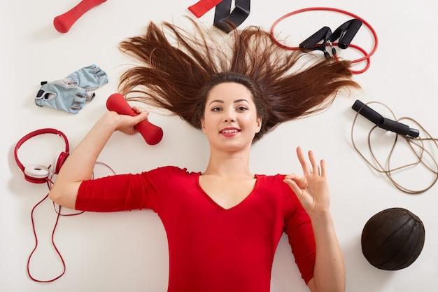 Feche o retrato de mulher esporte deitado na superfície branca com expressão facial feliz, fazendo mostrando sinal de ok e segurando halteres vermelho na mão, posando com diferentes equipamentos necessários para o treinamento.
