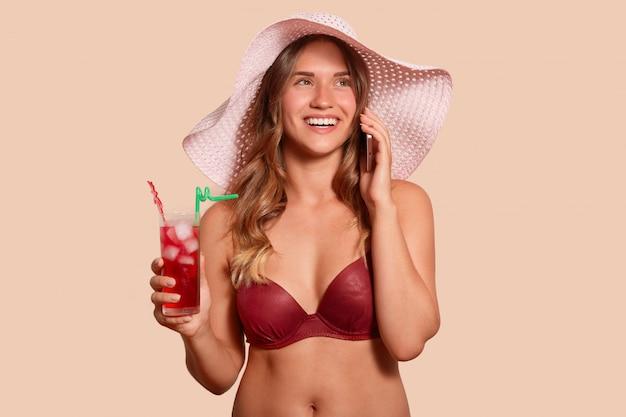 Feche o retrato de mulher europeia magnética alegre sendo de férias, vestindo calção e chapéu, segurando cocktail e smartphone em ambas as mãos, falando por telefone. conceito de pessoas e emoções.