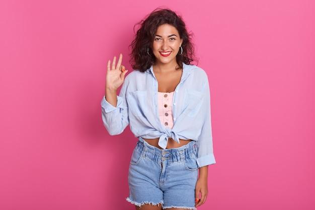 Feche o retrato de mulher feliz mostrando sinal de ok com a mão
