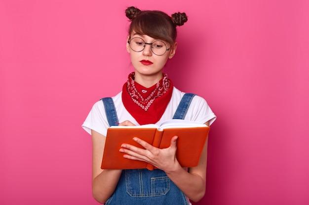 Feche o retrato de mulher jovem, atraente adolescente com cachos mantém o caderno nas mãos, anota algumas informações, tem expraixão facial pensativa, poses isoladas sobre parede rosa.