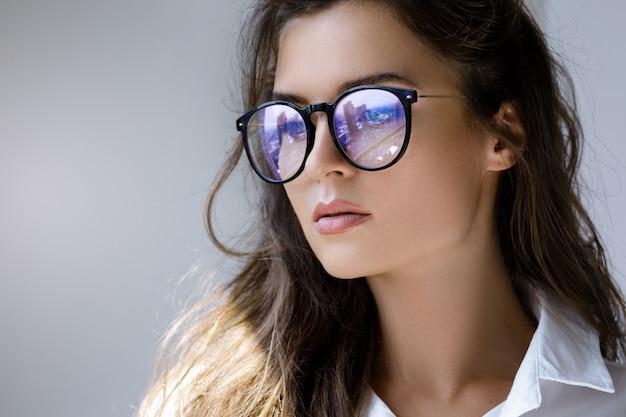 Feche o retrato de mulher jovem, com um reflexo da cidade moderna dentro de óculos