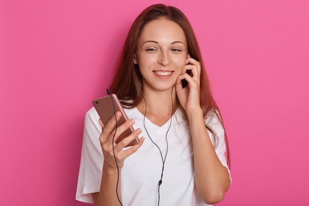 Feche o retrato de mulher ouvindo música usando telefone inteligente. morena caucasiana feliz energética fresca sobre rosa