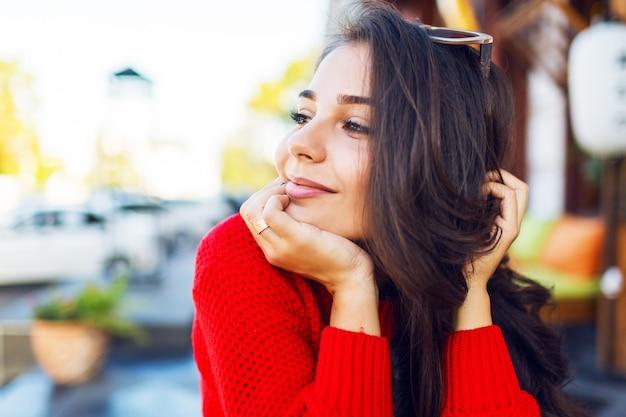 Feche o retrato de mulher romântica elegante com cabelos ondulados morenos com óculos de sol retrô elegantes e qua camisola de malha. fêmea de refrigeração no café moderno de manhã e beber café.