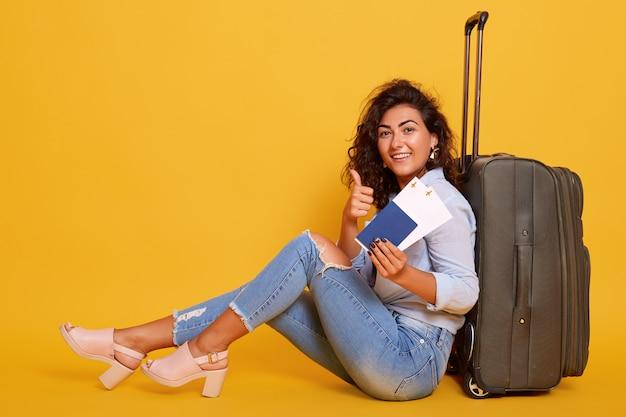 Feche o retrato de mulher turista esperando o voo, sentada no chão perto de sua mala cinza, segurando os documentos na mão, mostrando sinal de ok com o polegar, isolado sobre o amarelo