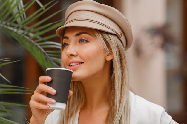Feche o retrato de outono de uma mulher loira romântica tomando um café quente ao ar livre