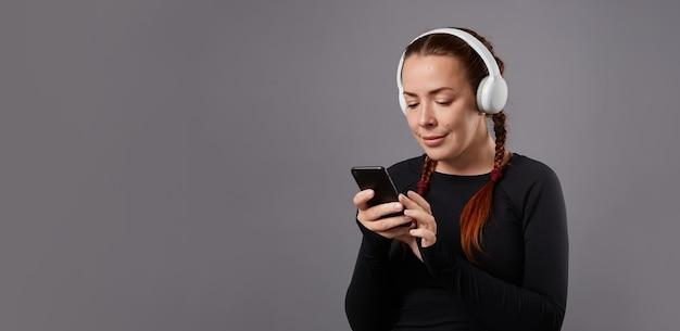 Feche o retrato de podcast feminino caucasiano ou música ouvindo em fundo cinza. ouvindo música em fones de ouvido