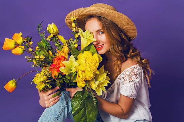 Feche o retrato de primavera da bela loira jovem elegante chapéu de verão palha segurando o buquê de flores de primavera colorida perto do fundo da parede roxa.