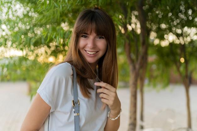 Feche o retrato de rir feminino europeu em t-shirt branca, posando no parque.