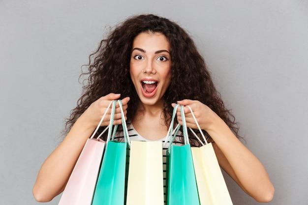 Feche o retrato de shopaholic feminino animado fazendo compras, sendo feliz e encantado para comprar produtos favoritos, segurando compras nas mãos
