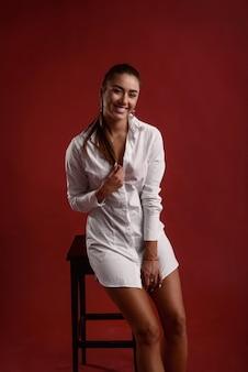 Feche o retrato de smilling atraente garota sexual com pernas perfeitas vestida camisa casual branca senta-se na cadeira preta contra o vermelho.