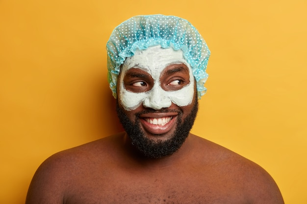 Feche o retrato de um cara feliz de pele escura usando chapéu de banho e aplicando máscara cosmética de argila
