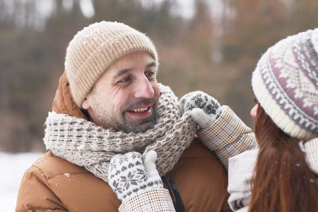 Feche o retrato de um casal adulto feliz ao ar livre no inverno com uma mulher carinhosa, ajustando o lenço no marido, copie o espaço