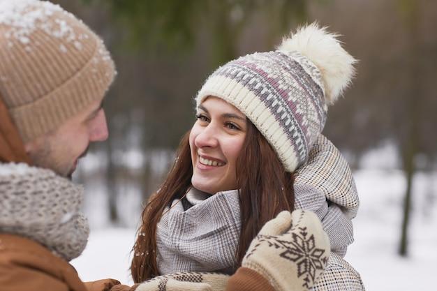 Feche o retrato de um casal adulto feliz ao ar livre no inverno com uma mulher sorridente, olhando para o marido, copie o espaço
