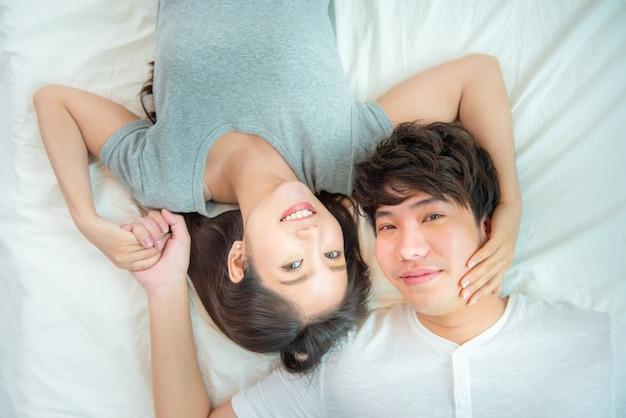 Feche o retrato de um casal asiático muito jovem com felicidade. mulher e homem da ásia deitem na cama de frente para a câmera com um sorriso grande toque de mão, emoção de amor com o conceito de dia dos namorados.