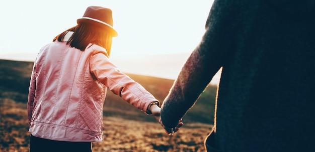 Feche o retrato de um casal caminhando em um campo durante uma tarde ensolarada de verão