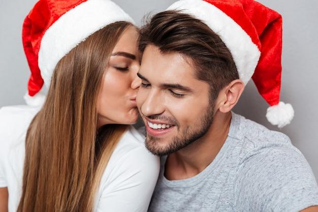Feche o retrato de um casal se beijando com chapéus de natal