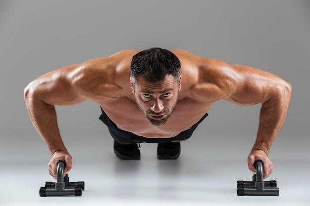 Feche o retrato de um fisiculturista masculino sem camisa forte confiante