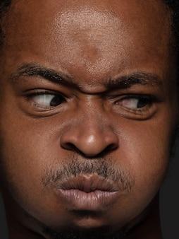 Feche o retrato de um homem afro-americano jovem e emocional. altamente detalhado modelo masculino com pele bem cuidada e expressão facial brilhante. conceito de emoções humanas.
