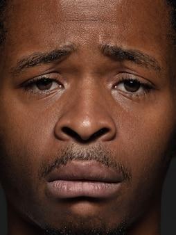 Feche o retrato de um homem afro-americano jovem e emocional. foto de modelo masculino com muitos detalhes, pele e expressão facial bem cuidadas conceito de emoções humanas. chateado, triste, desmotivado.