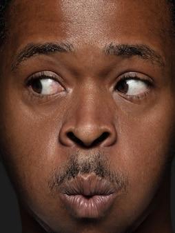 Feche o retrato de um homem afro-americano jovem e emocional. foto fotográfica altamente detalhada de um modelo masculino com pele bem cuidada e expressão facial brilhante. conceito de emoções humanas. olhando para o lado.