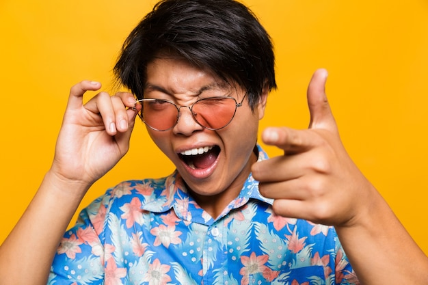 Feche o retrato de um homem asiático chocado de óculos escuros Foto Premium