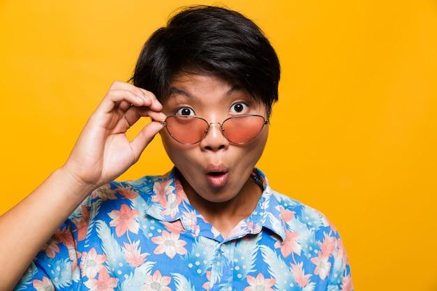 Feche o retrato de um homem asiático chocado de óculos escuros