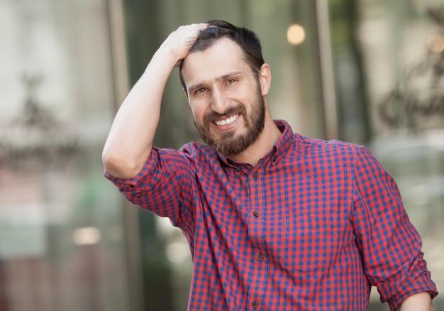 Feche o retrato de um homem atraente com barba rindo