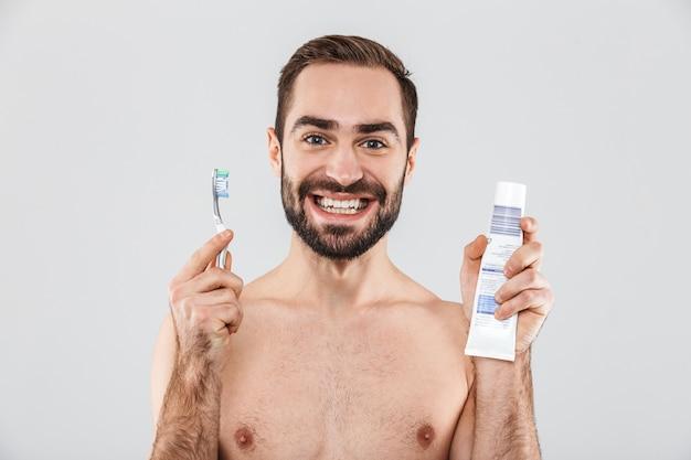 Feche o retrato de um homem barbudo bonito isolado sobre o branco, mostrando pasta e escova de dentes