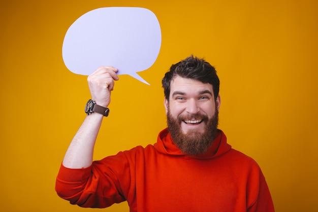 Feche o retrato de um homem barbudo espantado, segurando um discurso de bolha acima da cabeça.