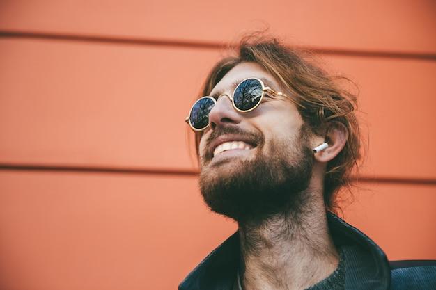Feche o retrato de um homem barbudo feliz em fones de ouvido