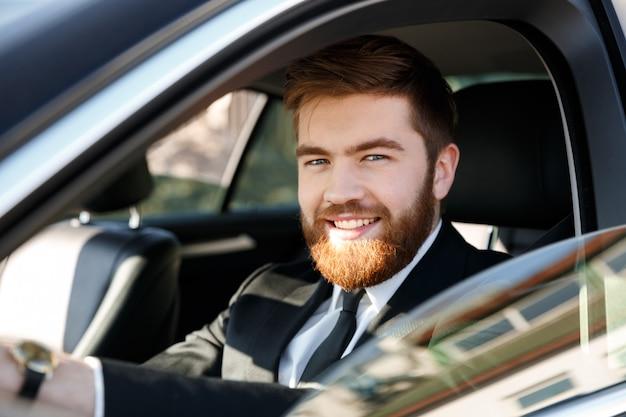 Feche o retrato de um homem barbudo sorridente em terno dirigindo carro